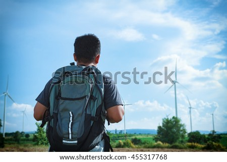 A man asian with backpack for travel and look at the view of the wind turbine .