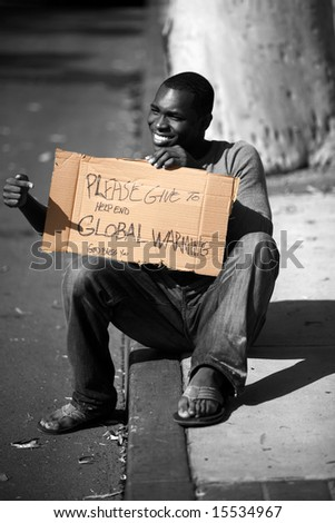 a man asks for donations to help stop Global Warming with his cardboard sign in black and white and colorized - stock photo