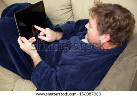 A man at home on his couch using this tablet PC.