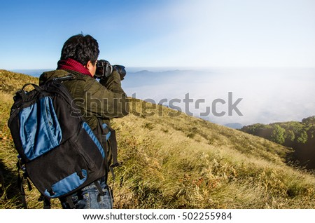 A man backpackers enjoying a valley view from top of a mountain