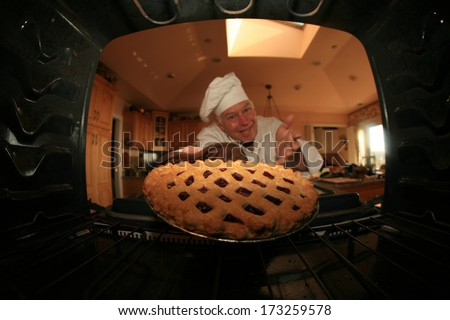 A Man bakes his signature Smiley Face Cookies in his oven for his hungry family and friends. Shot from the Inside of the oven facing out showing a unique view not often seen.  - stock photo