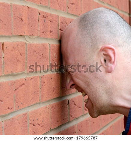 a man banging his head against the wall in frustration