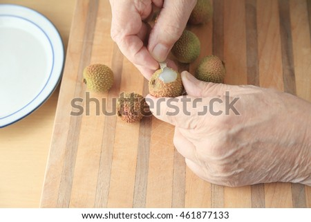 A man begins to peel a fresh lychee on a cutting board.