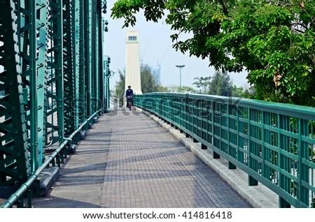 a man biking on bike lane along the bridge - stock photo