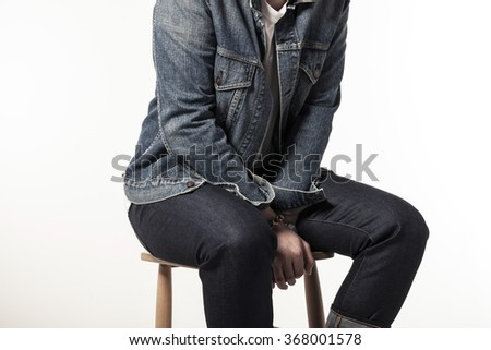 A man(boy, male, model) wearing blue denim(jeans) jacket and pants(trousers) sit down on the wood chair isolated white at the studio.