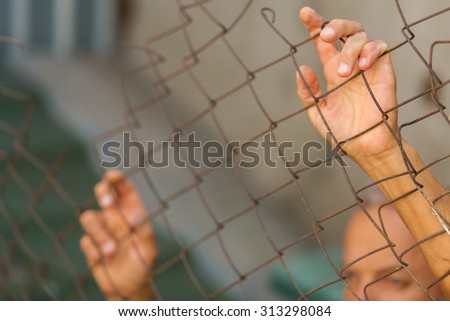 A man breaking down the fence. Immigration concept - stock photo
