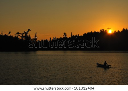 A Man Canoeing at Sunset on a Remote Wilderness Lake - stock photo