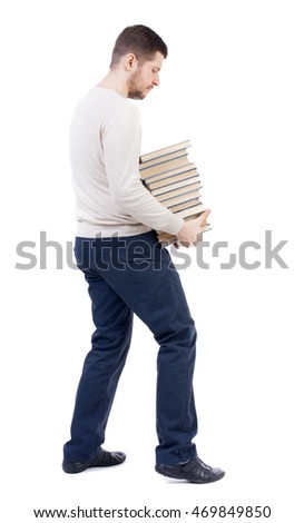 A man carries a heavy pile of books. back view. Rear view people collection.  backside view of person.  Isolated over white background. The bearded man in a white warm sweater, tries to comfortably