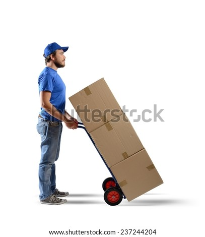 A man carries boxes in a cart - stock photo