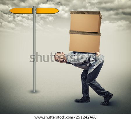 A man carries two heavy boxes - stock photo