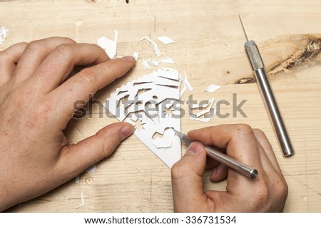 A man carves a snowflake out of paper - stock photo
