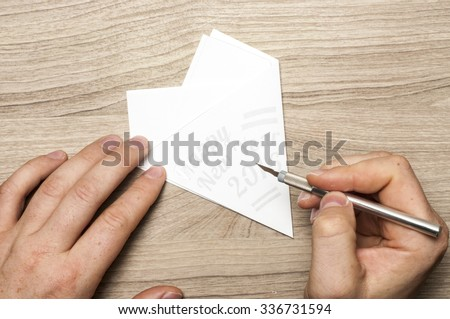 "A man carves a snowflake, with sign ""Happy New Year"", out of paper - stock photo"
