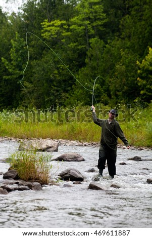 A man casts a fly rod in a river.