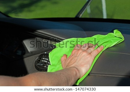 A man cleaning a dashboard with a green rag - stock photo