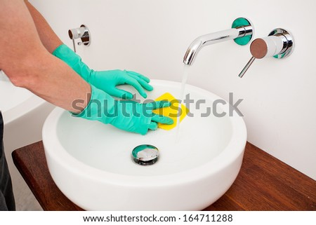 A man cleaning a sink with a yellow rag - stock photo