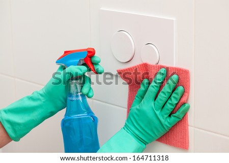 A man cleaning a toilet cistern using a rag and spray cleaner - stock photo