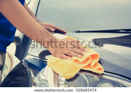 A man cleaning car with microfiber cloth, vintage tone image - stock photo