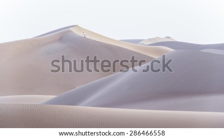 A man climbing a dune in the desert of Chigaga, Morocco - stock photo
