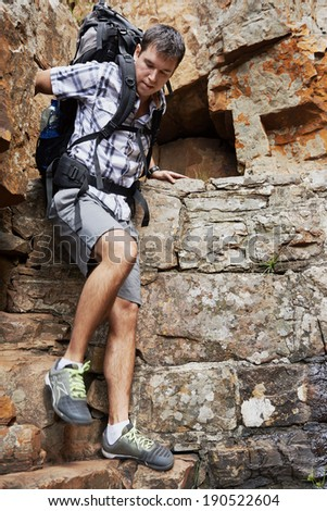 A man climbing down a steep mountain with copyspace - stock photo