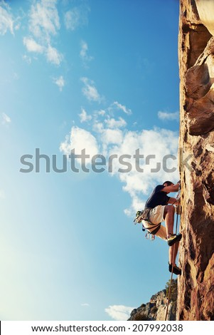 A man climbing up a really steep mountain attached to a harness and rope looking up against a blue sky in the outdoors - stock photo