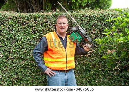 A man conducting his chores by trimming vines along a wall. - stock photo