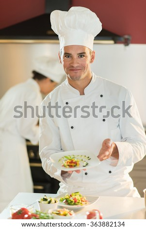 A man cook chef in his fifties is standing in a professional kitchen presenting a plateful with fine food. He is looking at camera, wearing white chef clothes and hat. Shot with blurred background. - stock photo
