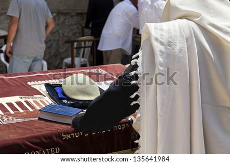 A man covered in a Jewish praying shawl praying in front of the wailing wall in the old city of Jerusalem.