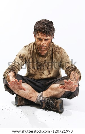 A man covered in mud sitting on the floor, trying to survive