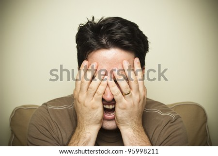 A man cries out in pain holding his face - stock photo