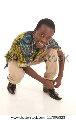 A man crouching down to tie his shoe with a smile on his lips
