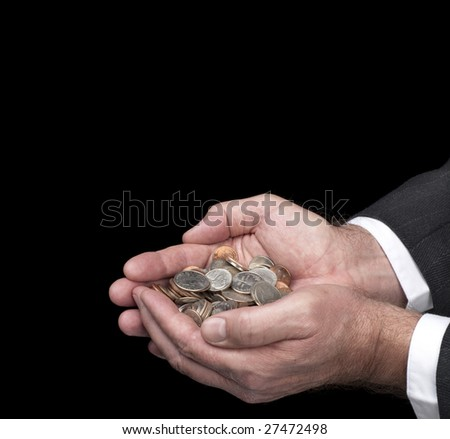 A man cups his hands as he holds a pile of coins.  Image was shot against a black backdrop and is not a cutout. - stock photo