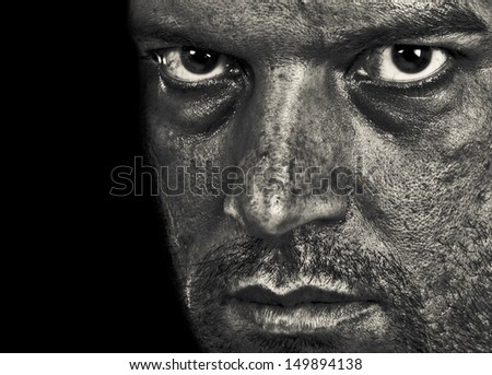 A man depressed showing emotion and evil in the intense eyes. In Black and White. - stock photo