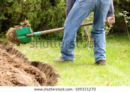 A man digging in the garden soil. - stock photo