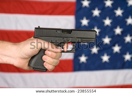 A man displays his semi automatic pistol against an American flag. - stock photo