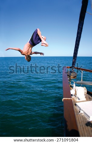A man doing a backflip into the ocean off the bow of a yacht. - stock photo