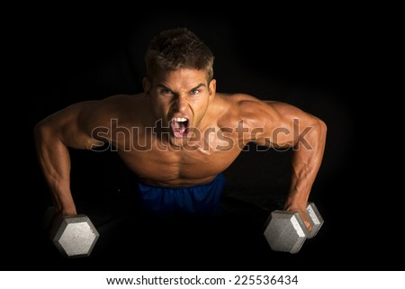 A man doing a push up on weights with is muscles flexing. - stock photo