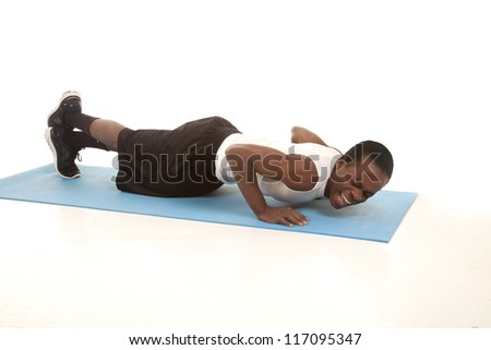 A man doing a push up with a painful expression on his face.