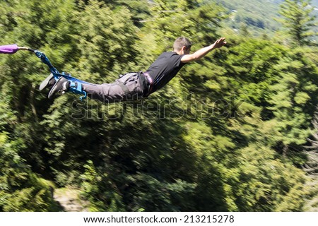 a man doing bungee jumping with a forest in background, extreme sports  - stock photo