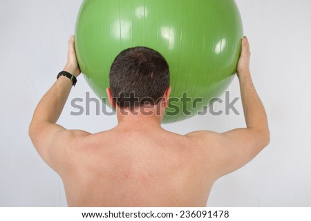 A man doing exercise with a swiss ball - stock photo