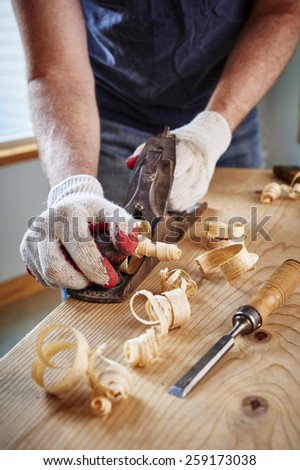 a man doing woodwork by using an old plane - stock photo