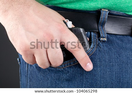 A man draws a small concealed handgun out of his pocket - stock photo