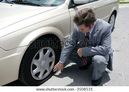 A man dressed for a business meeting discovering a flat tire on his car. - stock photo