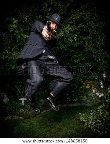 A man dressed in a vintage style suit and aiming a gun jumping in mid-air. - stock photo