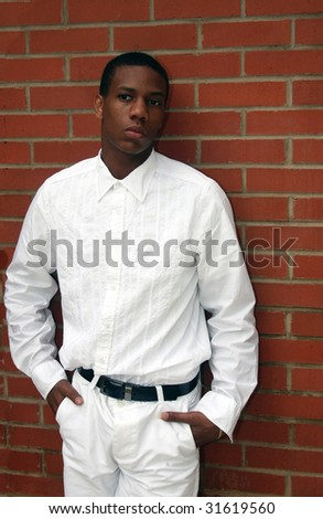 A man dressed in white standing by brick wall