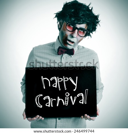 a man dressing a zombie costume with a black signboard with the text happy carnival written in it - stock photo