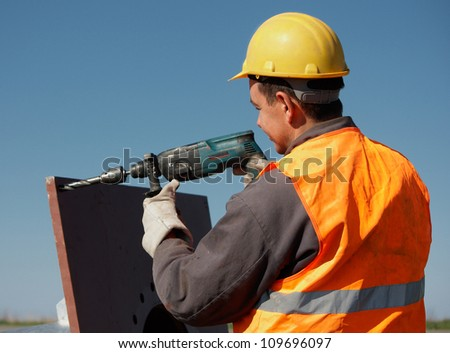 A man drilling a hole in a plate of metal, focus on man