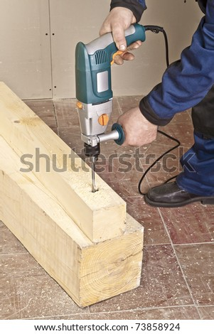 A man drilling a hole in wooden block