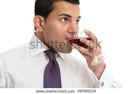 A man drinking or wine tasting from a glass filled with wine - stock photo