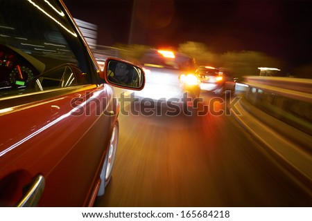 A man driving a car at night on a straight road.  - stock photo