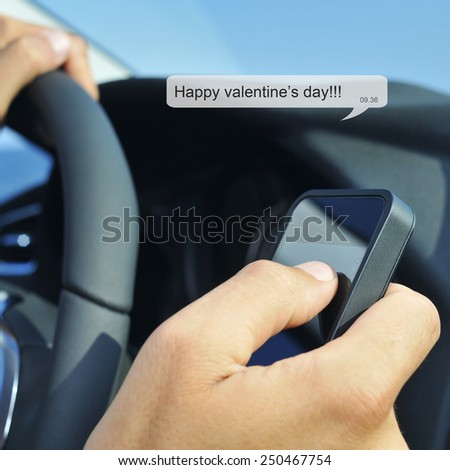 a man driving a car reads or sends the text message: happy valentines day - stock photo